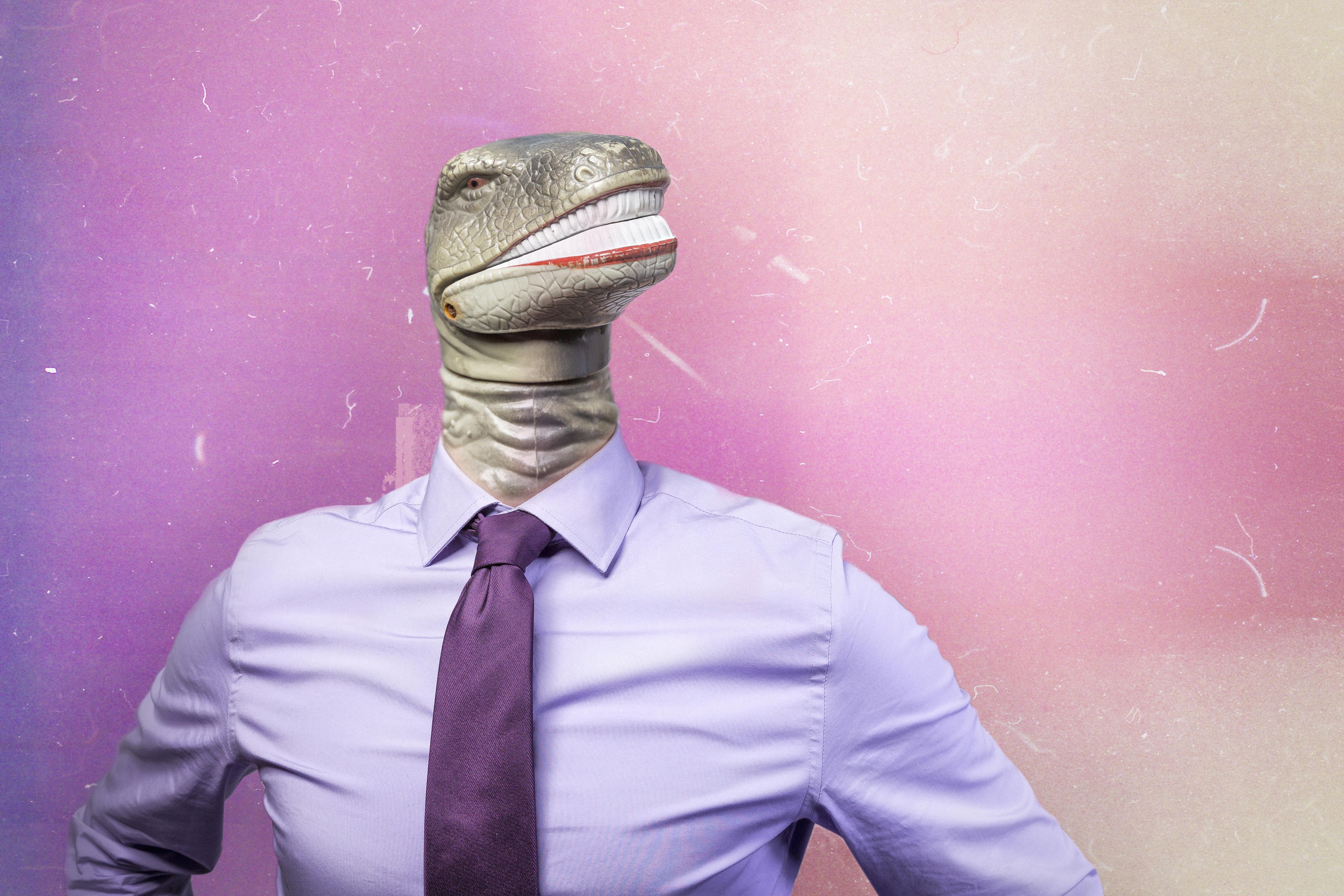 Personne avec une tête de serpent et un costume avec cravate ayant un air hautain
