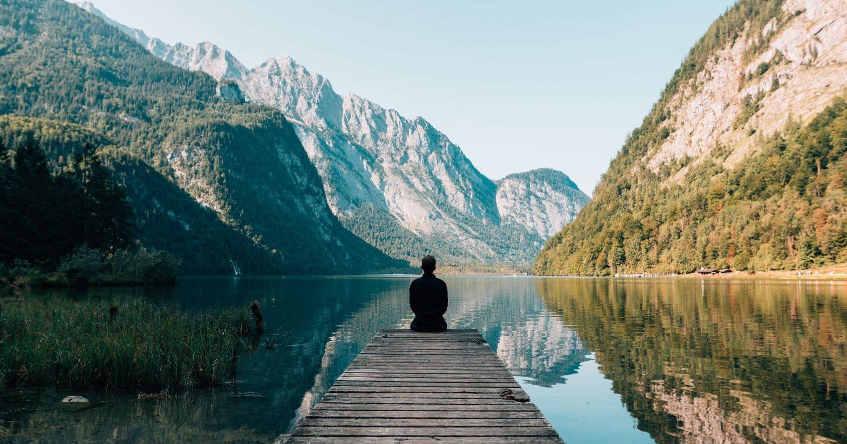 Personne de dos assise sur un ponton en bois qui regarde un paysage fait de montagnes et d'eau