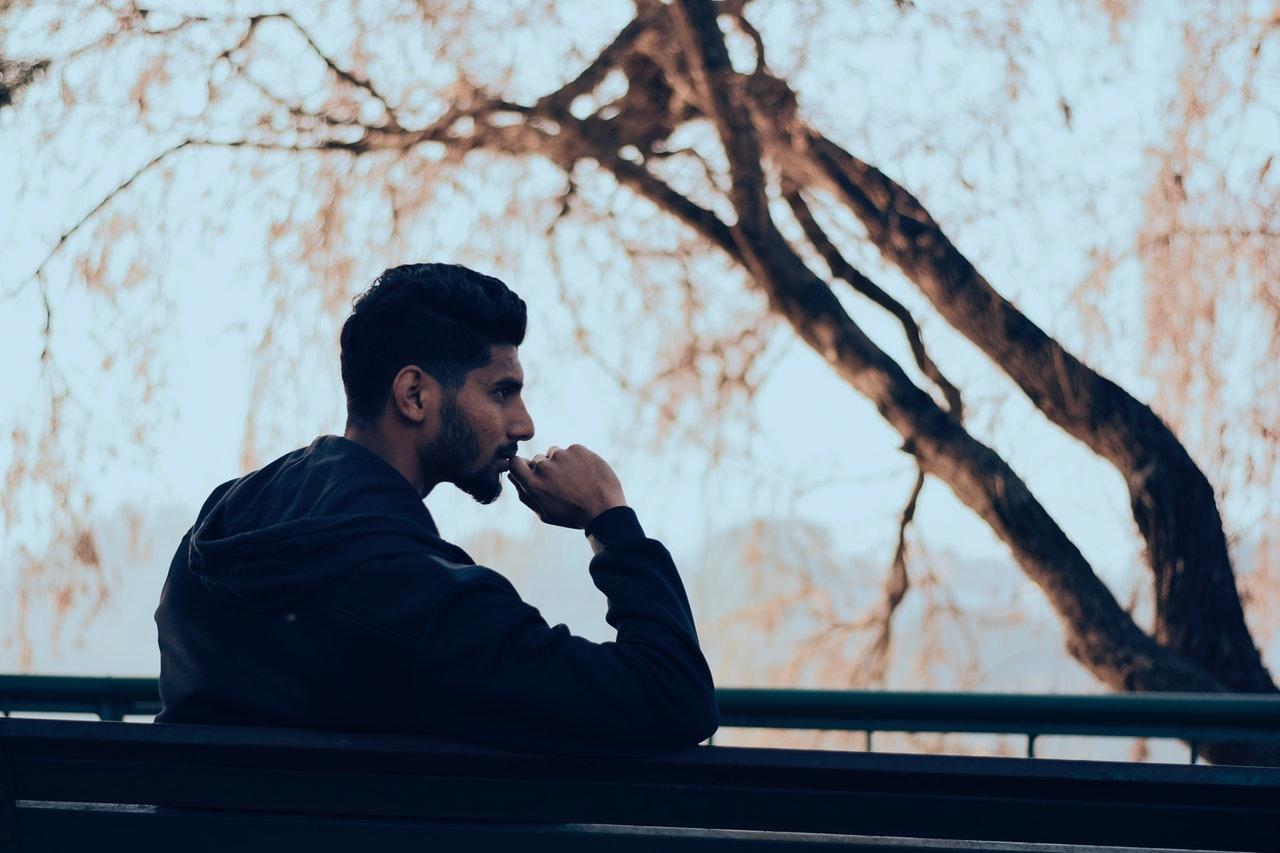 Homme assis sur un banc qui réfléchit