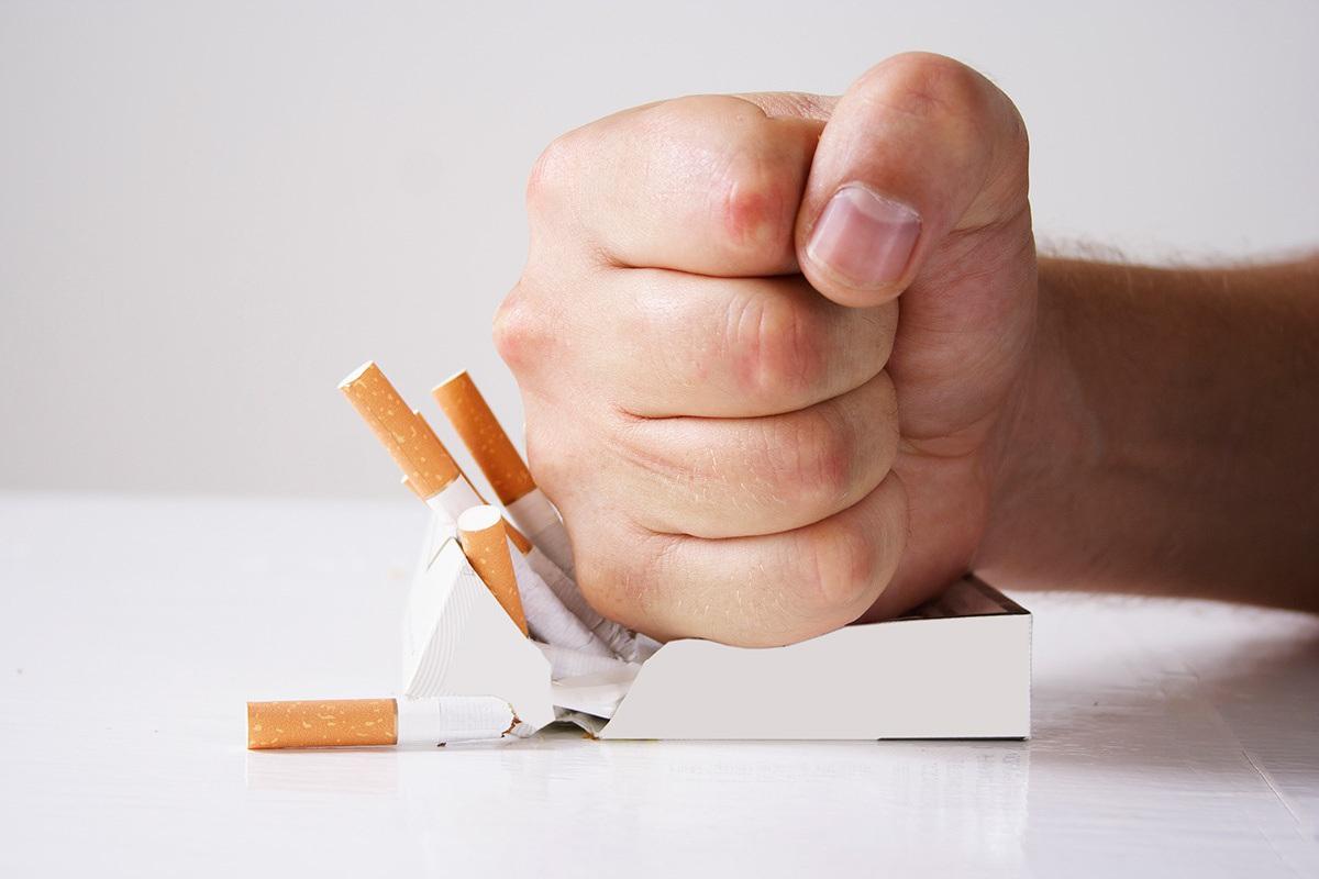 Poing fermé qui écrase un paquet de cigarettes