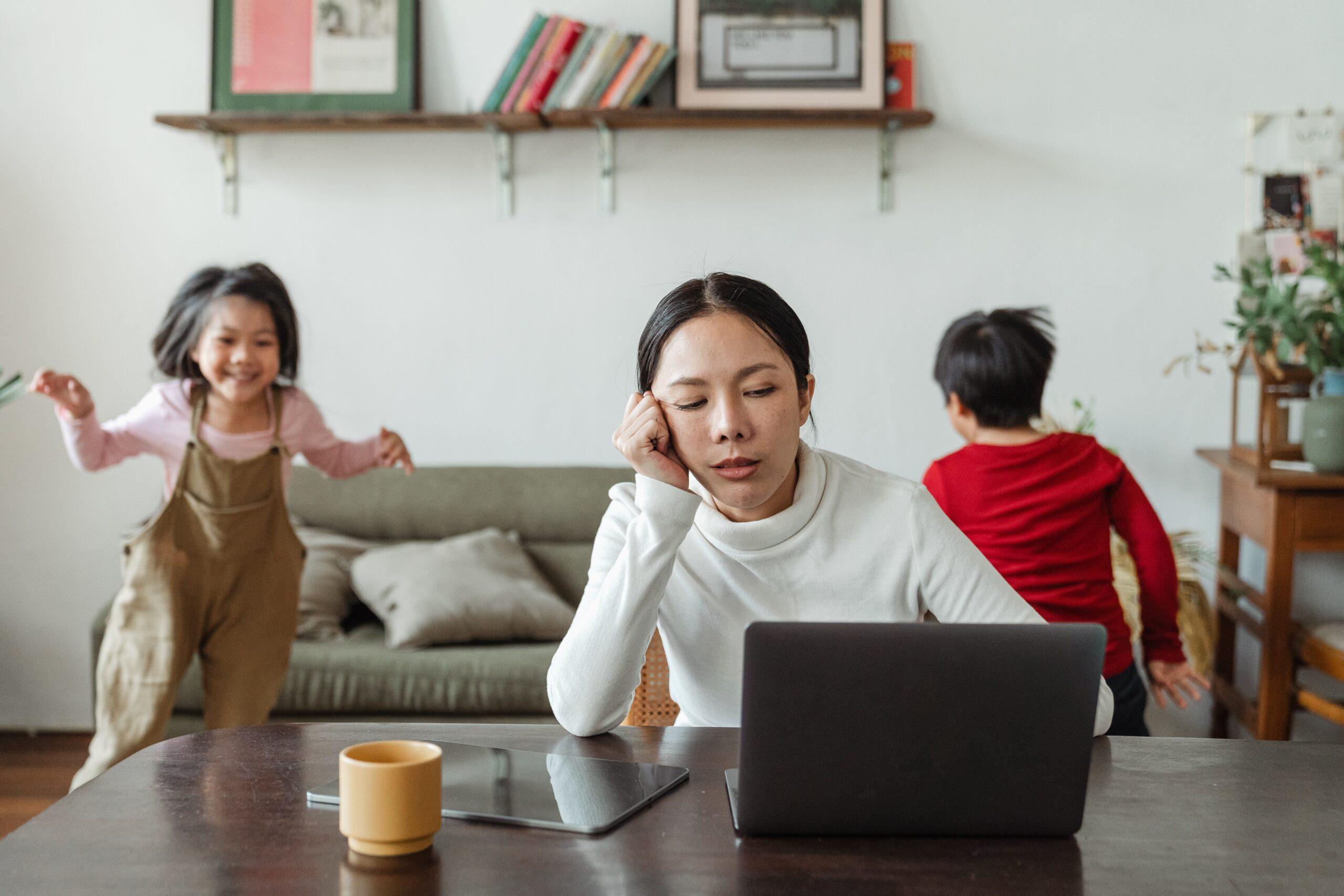 Une maman fatiguée qui a sa tête posée sur son bras droit devant son ordinateur et son café pendant que les enfants courent derrière