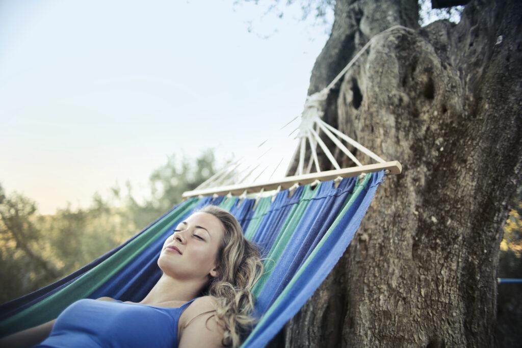 Une jeune femme qui dort dans un hamac accroché à un arbre