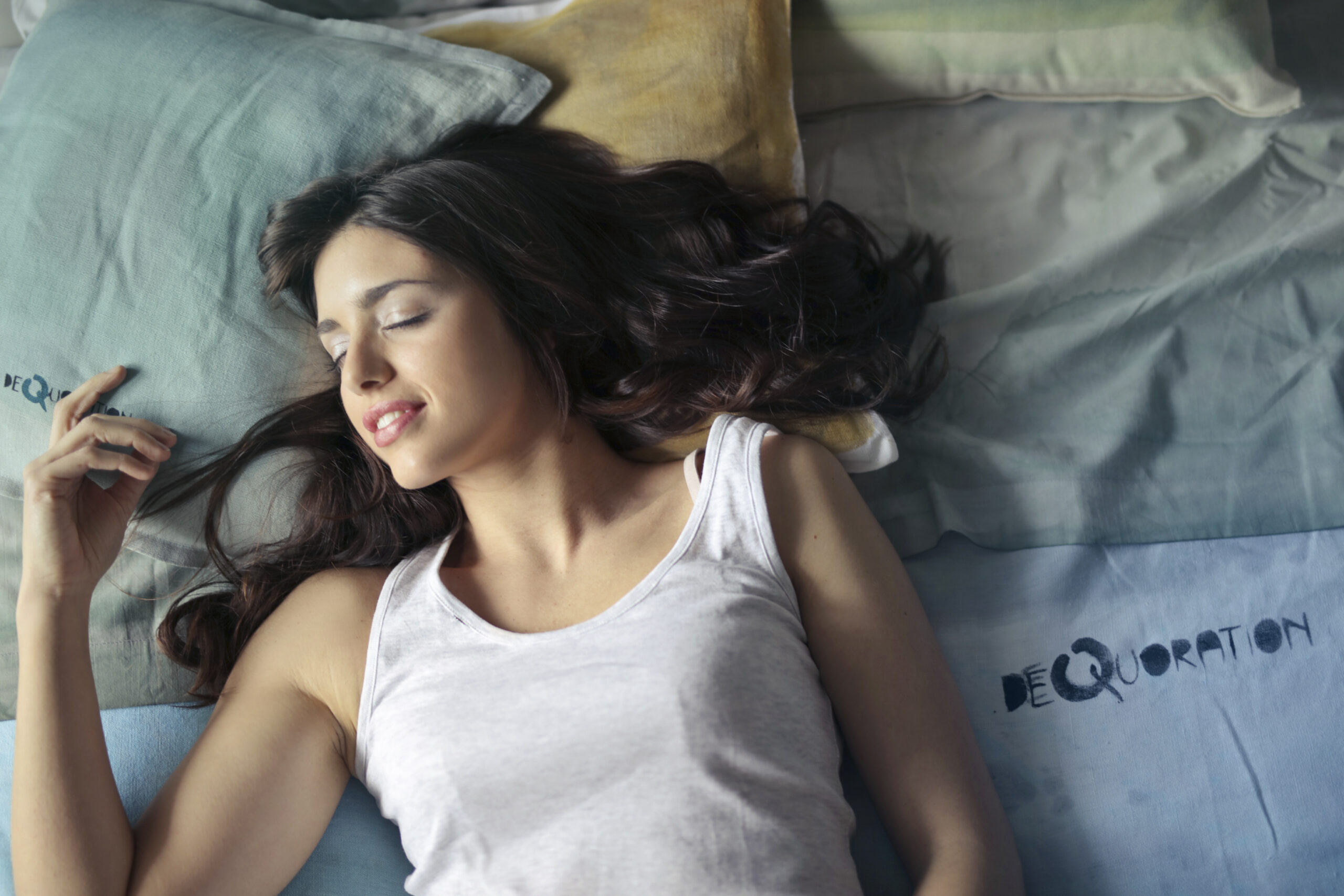 Photo d'une femme qui dort paisiblement dans un lit, la tête posée sur 2 oreillers