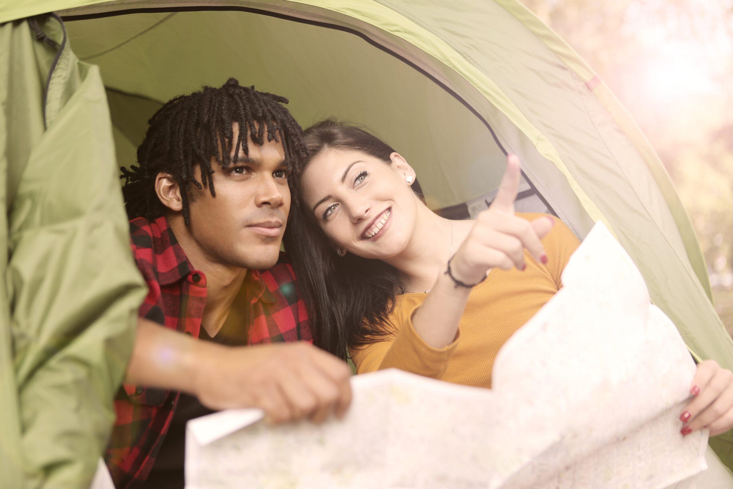 Un homme et une femme dans une toile de tente. Ils regardent une carte et la femme montre au loin avec son index