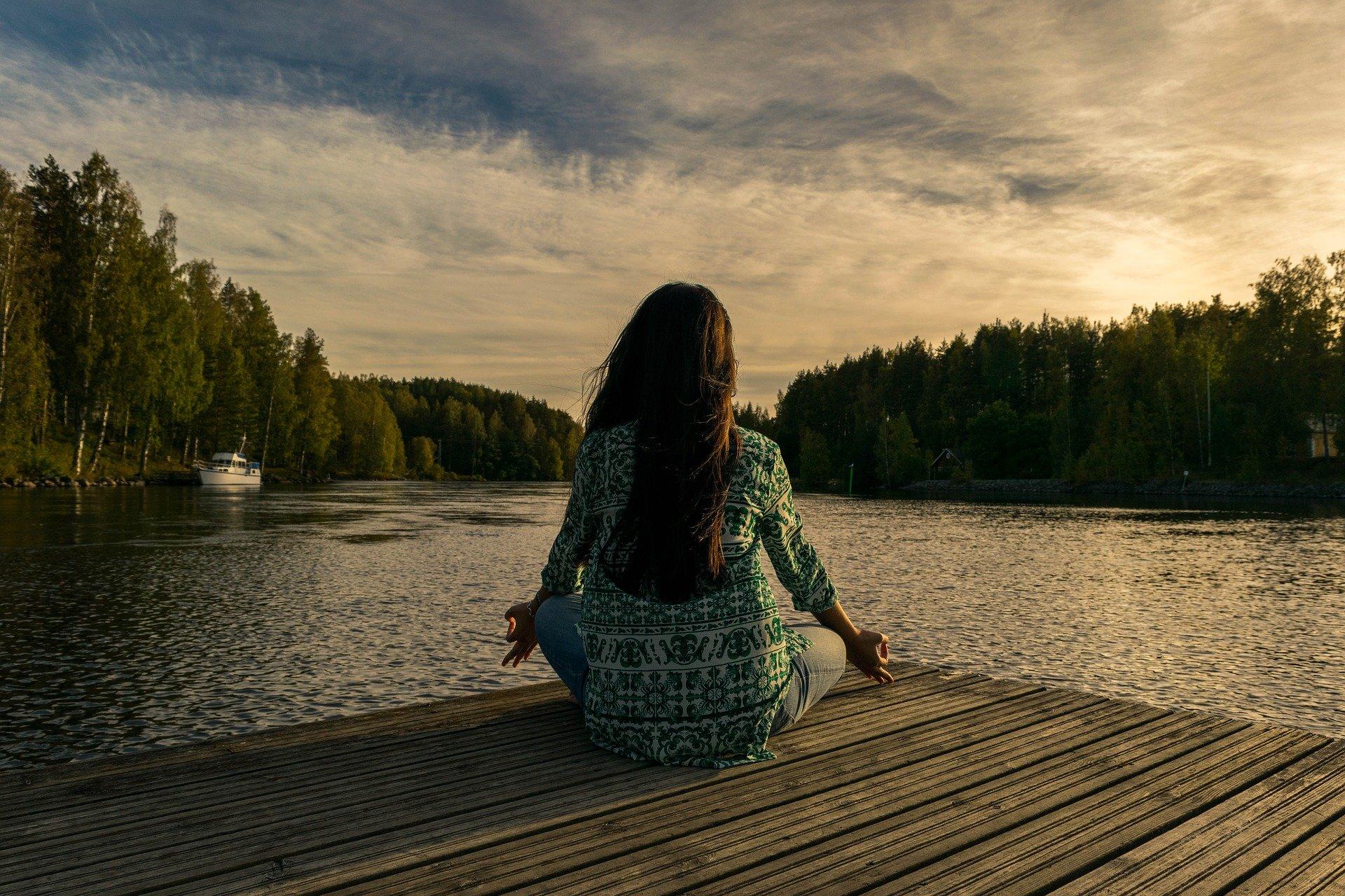Jeune femme de dos qui médite devant un lac