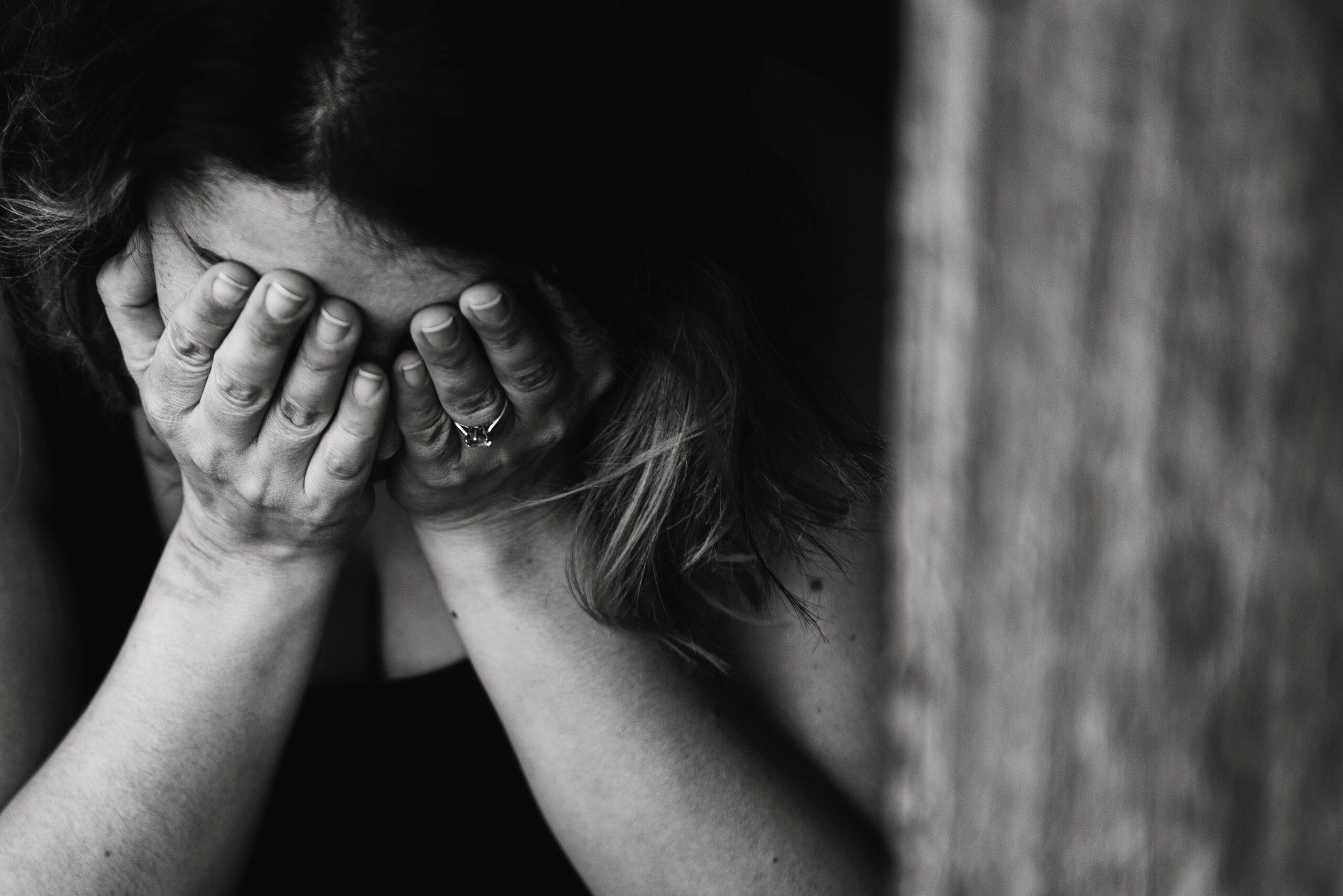 Femme triste qui met ses mains devant ses yeux