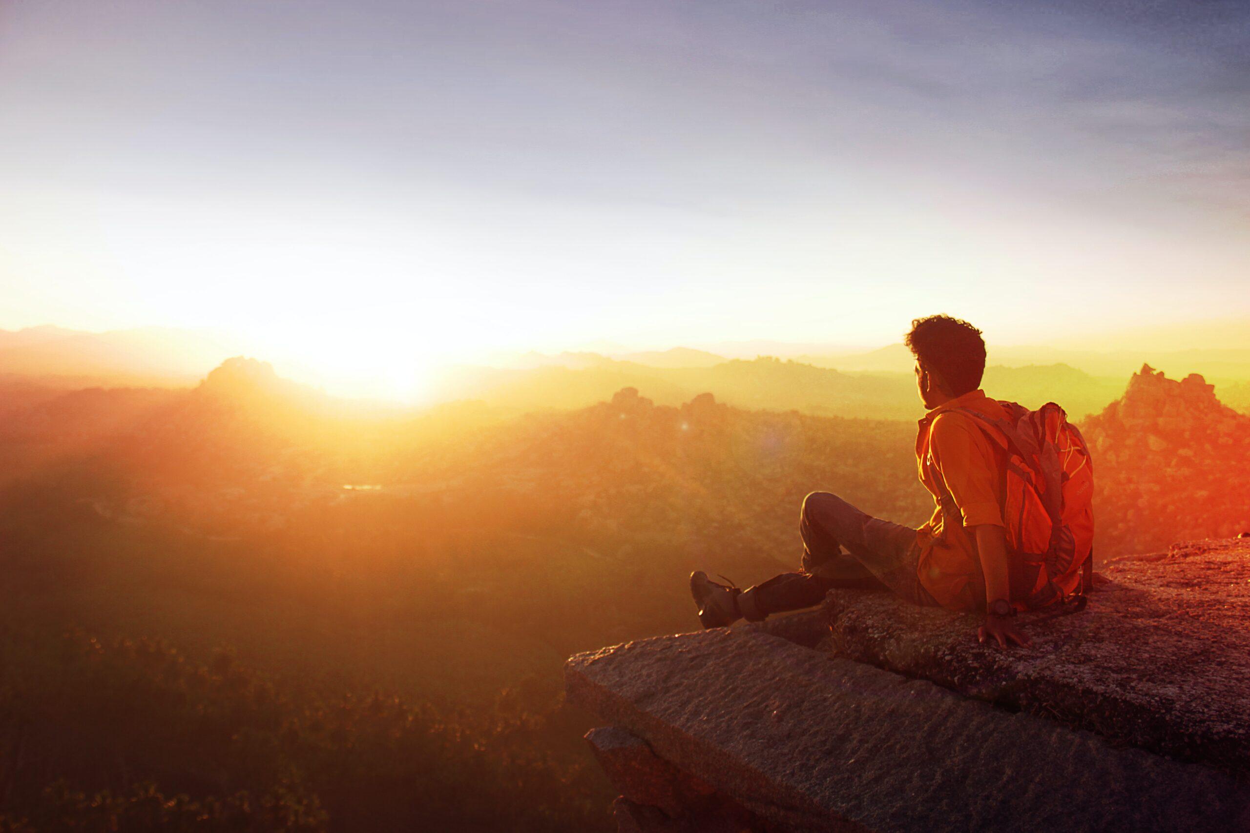 Homme assis sur une pierre qui regarde le soleil au loin à l'horizon